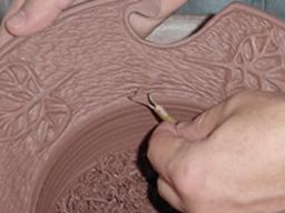Mike Ware decorates his work by incising and carving the clay surface.